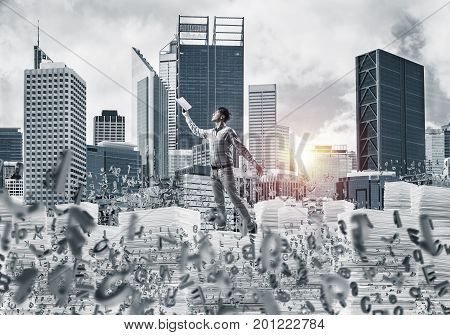 Side view of man in casual wear keeping hand with book up while standing among flying letters with cityscape and sunlight on background. Mixed media.
