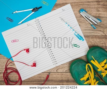 Notebook, Sneakers, Earphones, Paper And Other On Wooden Plank.