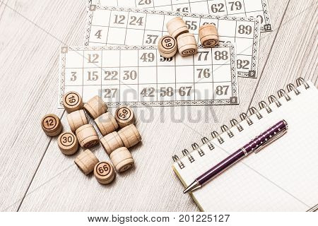 Board Game Lotto On White Desk. Wooden Lotto Barrels And Game Cards, Notebook With A Pen