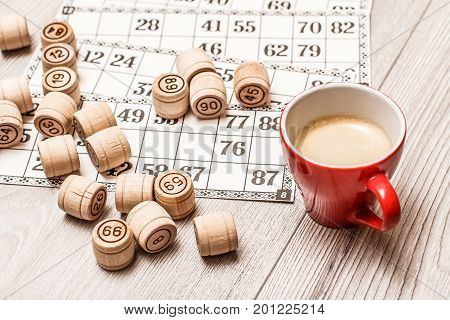 Board Game Lotto On White Desk. Wooden Lotto Barrels And Game Cards With Cup Of Coffee