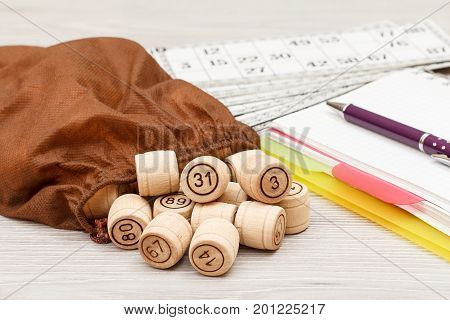 Board Game Lotto On White Desk. Wooden Lotto Barrels With Bag, Game Cards And Notebook With A Pen