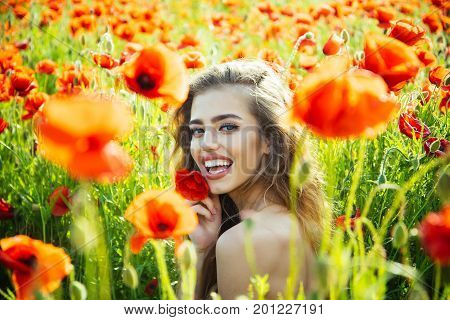 pretty woman or happy smiling girl with long curly hair hold flower in field of red poppy seed with green stem on natural background summer spring drug and love intoxication opium