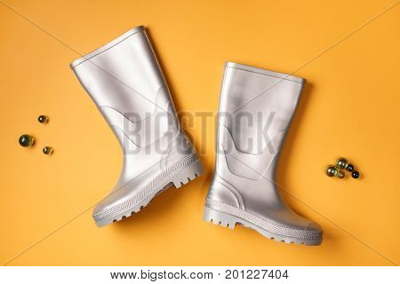 Autumn stylish set of silver gumboots and small glass balls. Yellow background Top view. Flat lay.