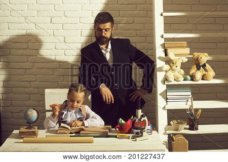 Kid And Man By Desk With School Supplies