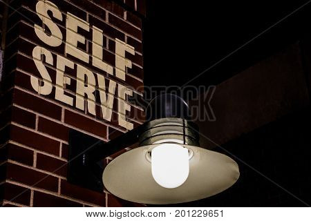self serve sign on brick wall with light