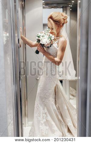 Gorgeous Bride In Hotel Elevator, Beautiful Female Bride In Elegant White Wedding Dress Posing In El