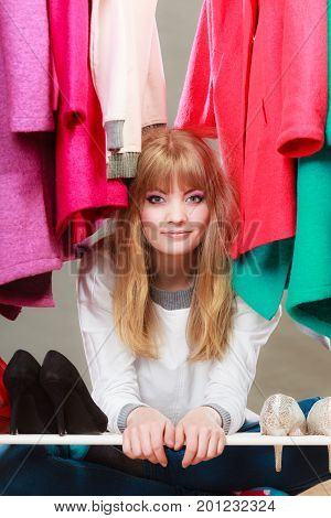 Pretty cute and charming woman sitting under clothing from wardrobe. Young happy undecided shopper girl bought new clothes. Sale concept.