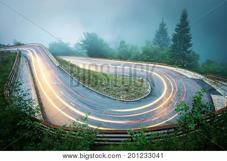 Hairpin curve mountain road with car lights in night. Dangerous driving conditions with fog, slippery surfacea and low visibility. Alps, Slovenia.