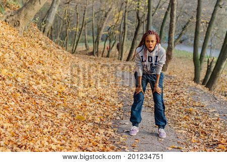African american girl after jogging in park. Autumn.