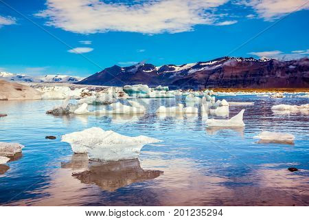 Icebergs and ice floes are reflected in the smooth water. Drift ice Ice Lagoon - Jokulsarlon. Morning in the Ice Lagoon, Iceland. The concept of extreme northern tourism