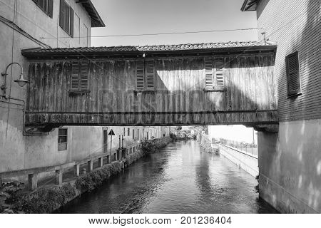 Gorgonzola (Milan Lombardy Italy): the canal of Martesana with historic buildings reflected in the water. The famous wooden bridge. Black and white