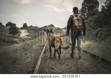 A woman with a backpack and her dog crossing the path of old rails in an apocalyptic sand dune world