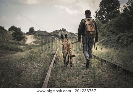 A dog and a woman walking in the dune between old rails in an apocalyptic world