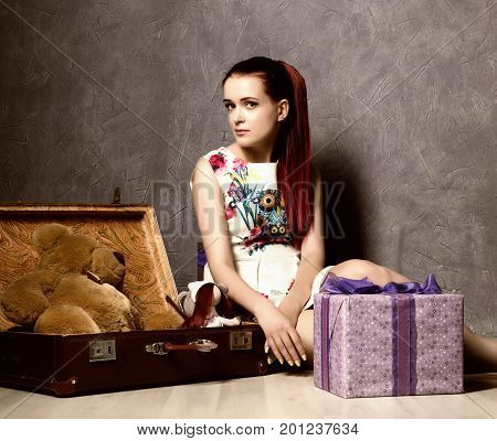 Beautiful young woman packing suitcase and getting ready for traveling, retro concept.