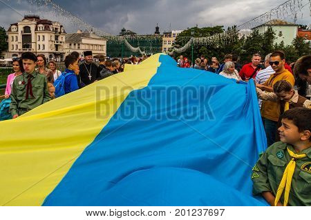 Uzhgorod Ukraine - August 23 2017: Townspeople and small scouts carry a 100-meter flag during the celebration of the Day of the State Flag of Ukraine in Uzhgorod.
