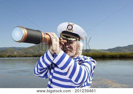 Captain looks through a telescope. Marine concept