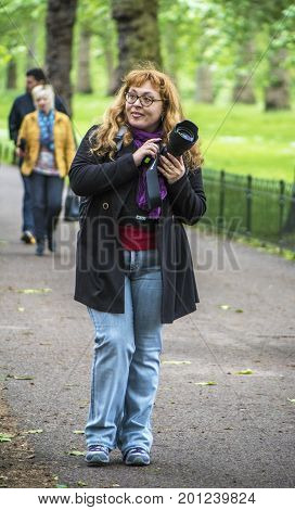 London, the UK - June 2016: smiling woman photographer in St James park