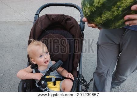 Crop shot of anonymous person with ripe watermelon and baby in carriage at street.