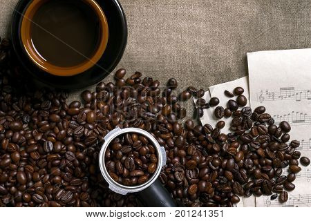 Coffee beans, sheet music and Coffee cup on a burlap background. Top view. Copy space. Still life. Mock-up. Flat lay