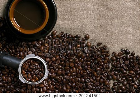 Coffee beans and Coffee cup on a burlap background. Top view. Copy space. Still life. Mock-up. Flat lay