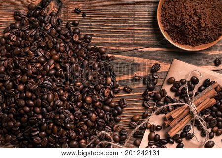 Coffee beans, cinnamon sticks and ground coffee on rustic wooden table, view from above with space for text. Still life. Mock-up. Flat lay