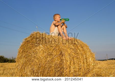 The boy sat in the field in the bundles of hay and drank water