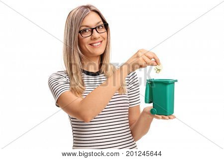 Young woman throwing a piece of garbage in a small bin isolated on white background