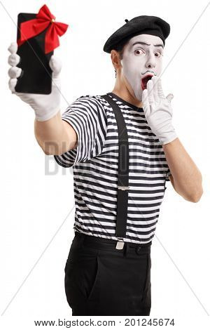Surprised mime showing a phone wrapped with red ribbon as a gift isolated on white background