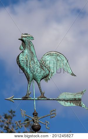 Big cockerel on a weathervane. Metal weather pointing north west. Traditional blue green windvane. Weathercock against sky.