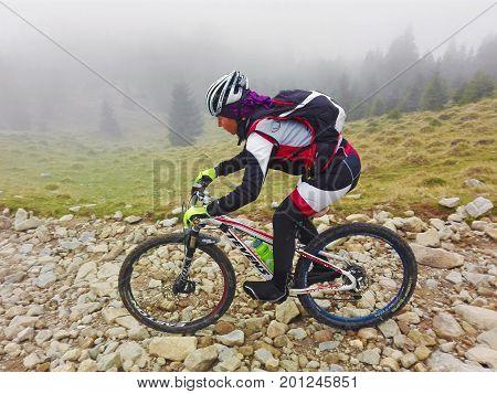 Tarcu Romania - October 29 2016: Woman mountain biker descending a rocky trail in the mountains. Shot taken on October 29th 2016
