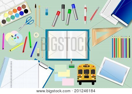 School supplies are lying around the open book on the green background. Free place for your text is in the open book.