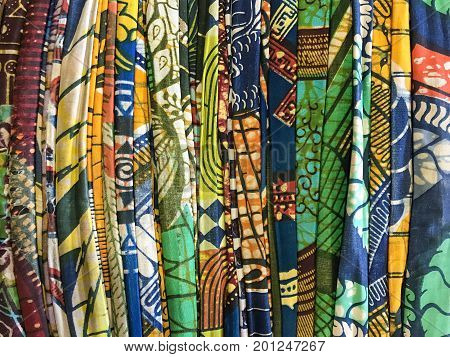 Pile of cotton fabric in variety of vibrant colors and patterns create beautiful abstract wallpaper or background
