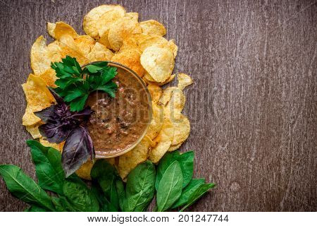 Potato chips with dipping sauce on a wooden table. Unhealthy food on a wooden background. Top view. Copy space. Flat lay. Still life