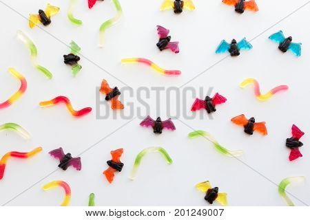 halloween, junk food and confectionery concept concept - multicolored gummy worms and jelly bet candies over white background