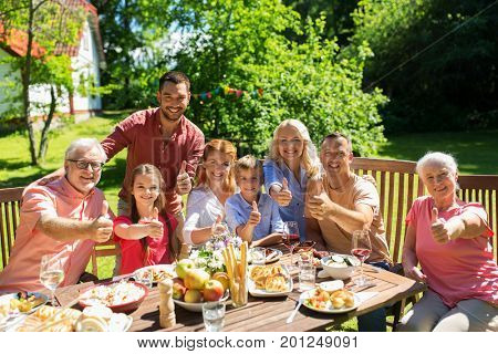leisure, holidays and people concept - happy family having festive dinner or summer garden party and showing thumbs up