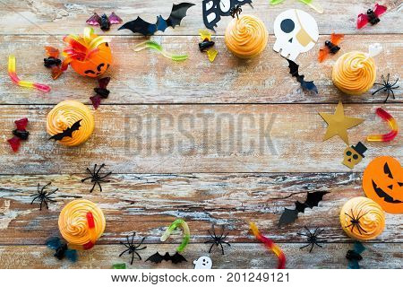 holidays, decoration and party concept - halloween paper decorations and treats with blank copy space over white background
