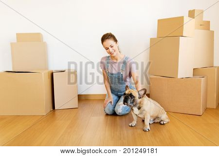 mortgage, people and real estate concept - happy young woman with dog and boxes moving to new home