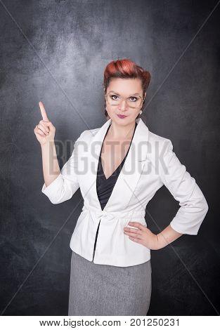 Skeptic Teacher In Glasses Showing On Something By Finger