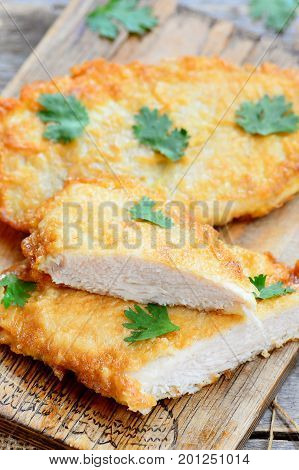 Fried chicken steaks in egg batter. Homemade chicken steaks on a wooden board. Easy chicken fillet recipe for dinner. Vertical photo. Closeup