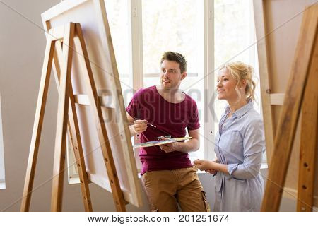 creativity, education and people concept - man artist or student with palette and woman teacher painting on easel at art school studio