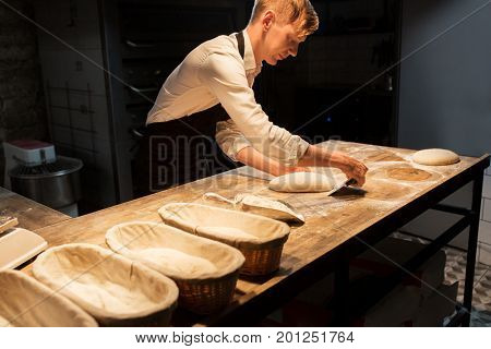 food cooking, baking and people concept - chef or baker making dough at bakery kitchen