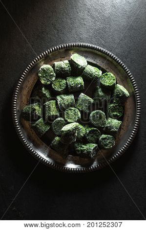 Frozen spinach in briquettes on a tin plate in the center of the table vertical