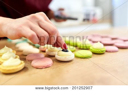 cooking, food and baking concept - chef decorating macarons shells at confectionery or pastry shop