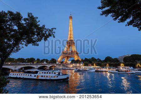 Paris, France - August 14, 2017. Famous french monument Eiffel Tower, cruise boats and bridge on Seine river by evening illumination.