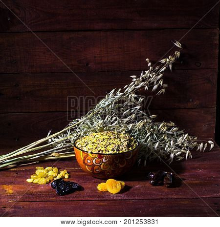 Cornflakes with raisins, dried apricots, prunes, dates on wooden background