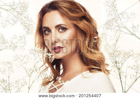Beautiful redhaired girl in white dress with a gentle romantic make-up and flowers. The beauty of the face. Portrait shot in the studio.