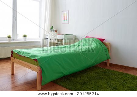 interior, home and furnishing concept - kids room with bed, table and accessories