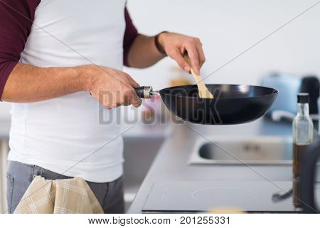 healthy eating, culinary and people concept - close up of man with frying pan cooking food at home kitchen