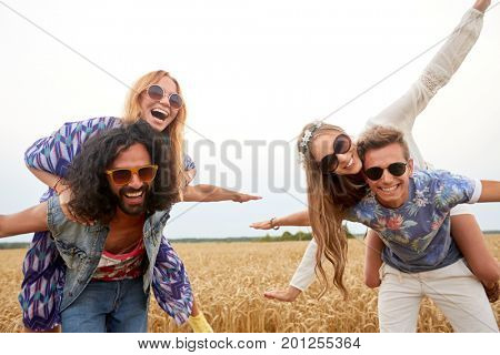 summer, youth culture and people concept - happy young hippie friends having fun on cereal field