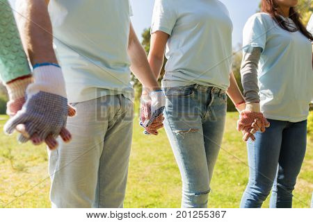 volunteering, charity, people and ecology concept - group of volunteers holding hands in park